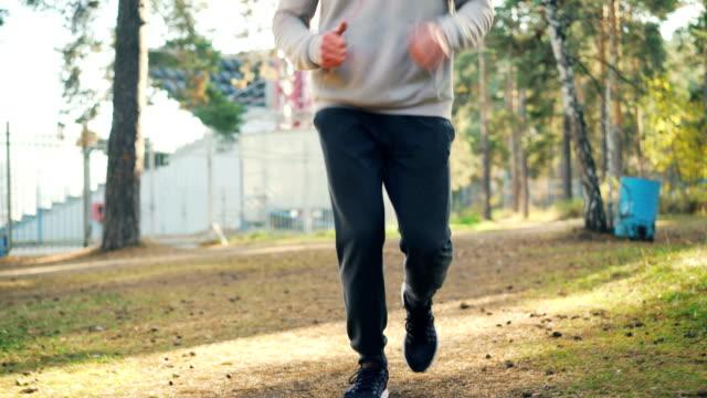 vídeos y material grabado en eventos de stock de incline-para arriba tiro de chico guapo en zapatillas y chándal jogging en el parque con los auriculares puestos y disfrutar de la actividad física y la naturaleza otoño. concepto personas y deportes. - sudadera