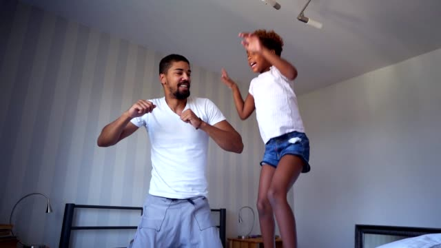 Time for fun with dad Dad and daughter jumping on the bed at home. ethnicity stock videos & royalty-free footage