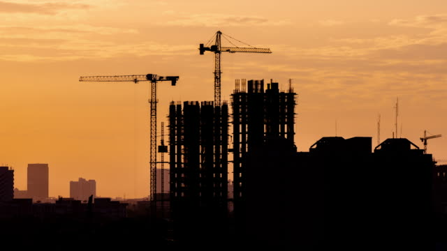 4K Time lapse: Aerial silhouette view of Construction Site, crane moving and sunset.