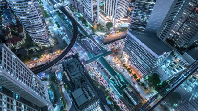 Time lapse Aerial view and top view of traffic on city streets in Bangkok , Thailand. Expressway with car lots. Beautiful roundabout road in the city center.