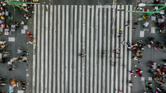 time lapse aerial view of pedestrians walking across with crowded traffic. - in cima video stock e b–roll
