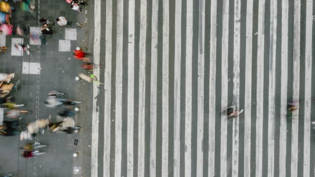 Time lapse aerial view of pedestrians walking across with crowded traffic.