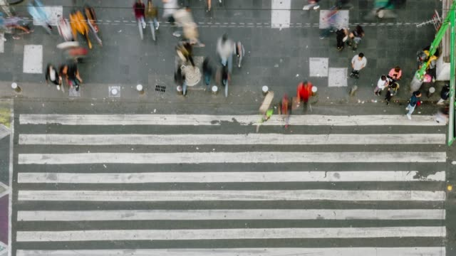 time lapse aerial view of pedestrians walking across with crowded traffic. - город мехико стоковые видео и кадры b-roll