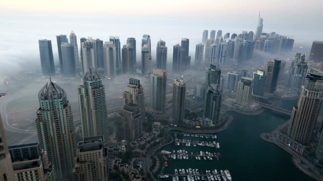 time lapse aerial view skyscraper foggy weather Dubai Marina at morning