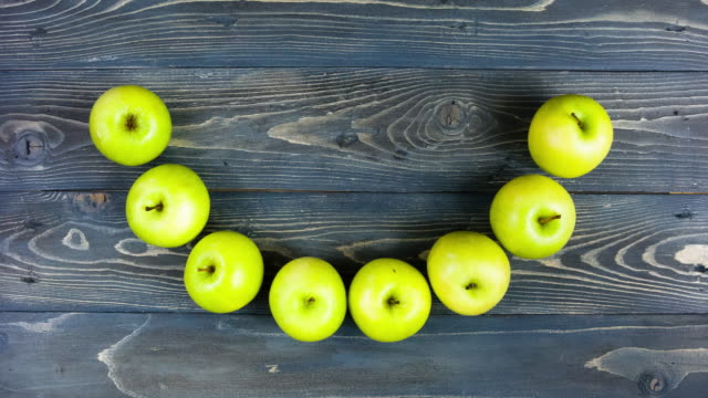 Time lapse animation of apple smile. Stop motion fresh fruits on wooden table, 4K. Concept for dentistry, fitness, healthy eating. video