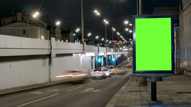 vídeos de stock e filmes b-roll de time lapse. billboard with a green screen, located on a busy street. cars move in the evening. - faixa sinal