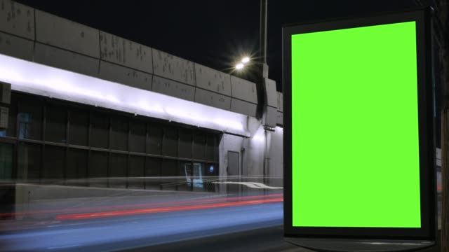 Time lapse. Billboard with a green screen, located on a busy street. Cars move in the evening.