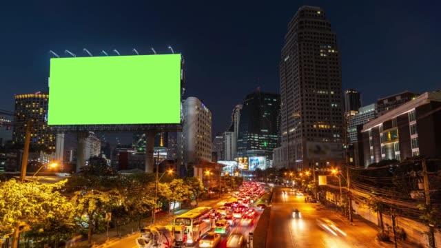 zeitraffer: billboard mit grünen bildschirm und stadt ampel hintergrund bei nacht. 4k auflösung. - plakat stock-videos und b-roll-filmmaterial
