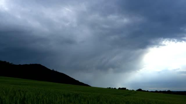 zaman lapse karanlık bir gökyüzünde bulutların bir buğday tarlasında bir tepe tarafından - sale stok videoları ve detay görüntü çekimi