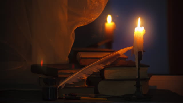 Time lapse candle and old books at night time. Close up view. Cinematic color grading