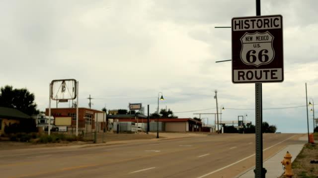 stockvideo's en b-roll-footage met 4k time lapse auto's rijden door de historische route 66 verkeersbord santa rosa (new mexico) - arizona highway signs