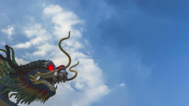 time lapse: drago cinese scultura con nuvole in movimento sullo sfondo - totem fair video stock e b–roll