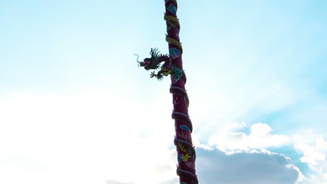 time lapse: drago cinese totem con raggio di sole e nuvole in movimento sullo sfondo - totem fair video stock e b–roll