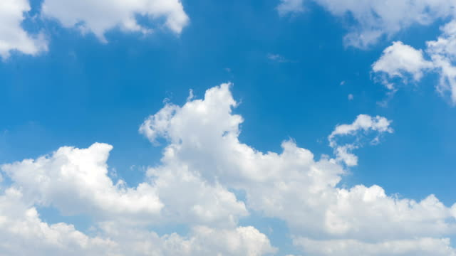 Time lapse clip of white fluffy clouds over blue sky video
