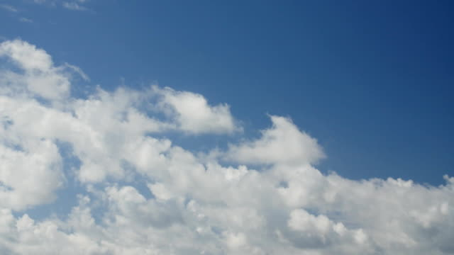 Bидео Time lapse clip of white fluffy clouds over blue sky