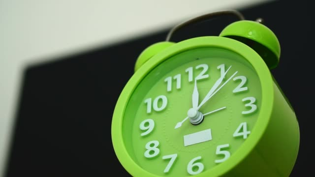 Time lapse, close up green alarm clock.