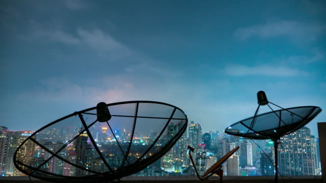 Time lapse close up Parabolic satellite dish with building at night video