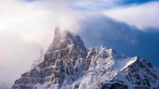 Time lapse clouds flowing over snowy mountain peak at sunrise video