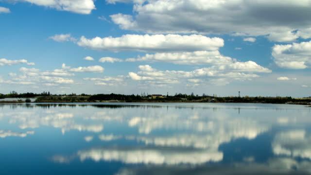 vídeos y material grabado en eventos de stock de nubes de lapso de tiempo moverse y reflejaron en fondo de mina de arena lago naturaleza - basalto