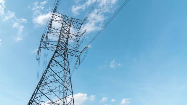 nuvole time lapse che si muovono attraverso il polo elettrico, torre elettrica ad alta tensione. - elettricità video stock e b–roll