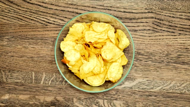 Time lapse. Crispy potato chips. Quantity reduction. Time lapse. Crispy potato chips. Quantity reduction. On the background of a wooden surface. potato chip stock videos & royalty-free footage