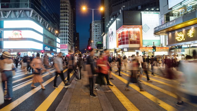 Time lapse crowd of Pedestrians walking and traffic car over the crosswalk in Mong Kok, Hong Kong