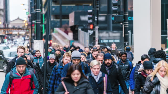 4k time lapse crowd of pedestrians walking on the street in rush hour among modern buildings in chicago, illinois, united states, business and american culture concept - tłum filmów i materiałów b-roll