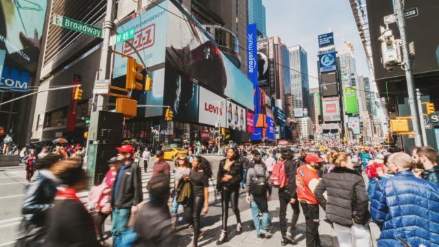 folla time lapse di turisti che camminano a times square - insegna commerciale video stock e b–roll