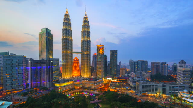 4k time lapse day to night of  elevated view of the petronas twin towers, during the evening, kuala lumpur, malaysia - malese video stock e b–roll