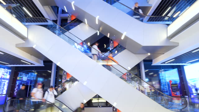 Time lapse escalators in modern shopping mall crowd of people. Very busy full of clients mall complex.