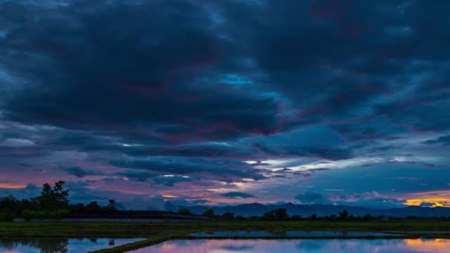 stockvideo's en b-roll-footage met 4k time-lapse: veld en prachtige zonsopgang en water reflectie op vijver in ochtend - regen zon