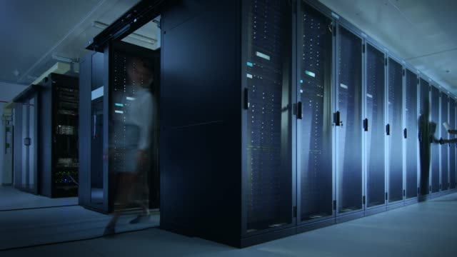 vídeos de stock e filmes b-roll de time lapse footage of it employees working in a data center server room. technicians and engineers running diagnostics and maintenance, inspecting server racks. - tecnologia