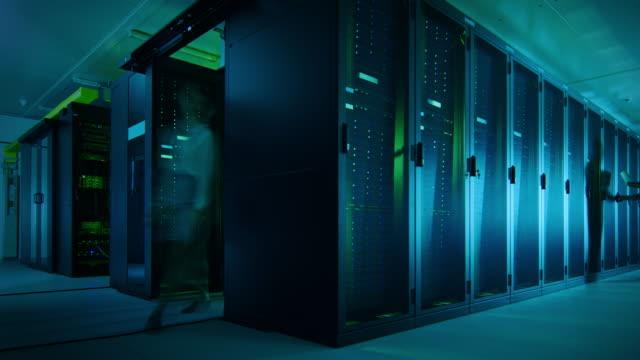 vídeos y material grabado en eventos de stock de tiempo secuencias de lapso de ti empleados trabajando en una sala de servidores del centro de datos. técnicos e ingenieros que ejecutan diagnósticos y mantenimiento, inspección de armarios para servidores. - equipo informático
