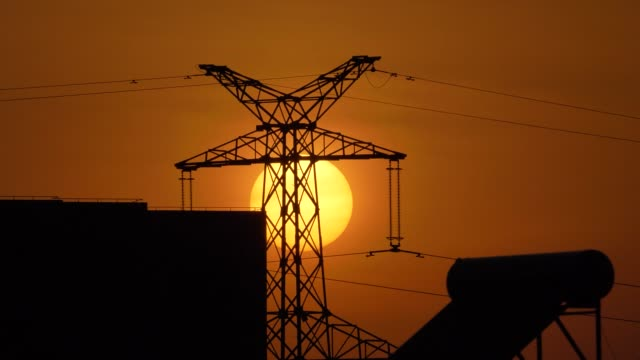 Time lapse footage of sunset with Silhouette of high-voltage power tower and city buildings, orange sun moving down, 4k b roll shot.