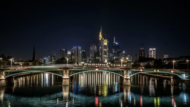 time lapse: frankfurt city is behind  stone bridge along main river, germany at night - francoforte sul meno video stock e b–roll