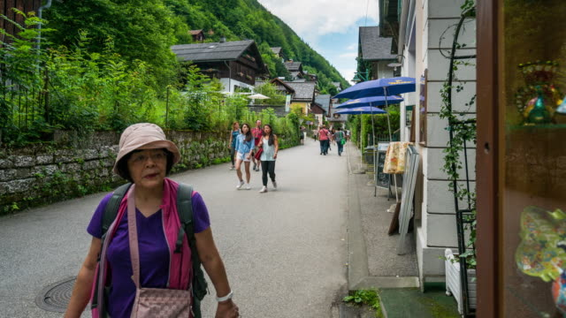 time lapse, landscape and crowd waking at hallstatt village, austria - neoclassical architecture stock videos & royalty-free footage