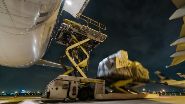 Time lapse loading cargo outside cargo plane at night video