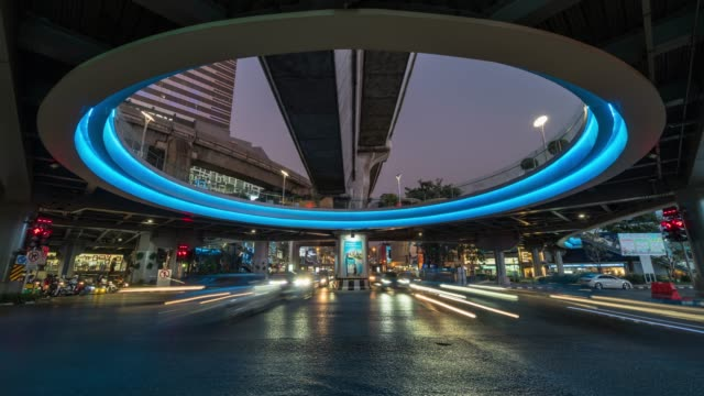 Time lapse long exposure of traffic jam and car crowd intersection in rush hour at night time in Bangkok, transportation with cityscape concept