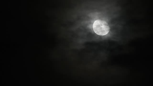 Time lapse motion Craters On The Surface Of The full moon In the dark sky and the black clouds at night Moving up fast.