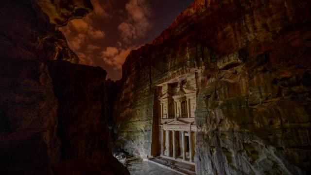 time lapse film av petra av natten, medan personer belysning ljus framsida skattkammaren (al-khazneh), mest genomarbetade templen i den gamla arabiska nabateanska kungarikets staden petra - fornhistorisk tid bildbanksvideor och videomaterial från bakom kulisserna
