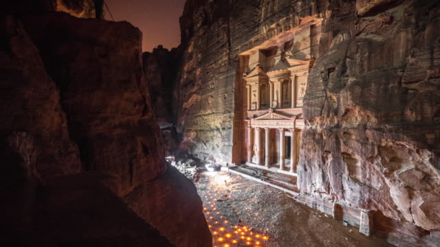 Time lapse Movie of Petra by Night, while people lighting candle front of The Treasury (Al-Khazneh), most elaborate temples in the ancient Arab Nabatean Kingdom city of Petra Time lapse Movie of Petra by Night, while people lighting candle front of The Treasury (Al-Khazneh), most elaborate temples in the ancient Arab Nabatean Kingdom city of Petra treasury stock videos & royalty-free footage