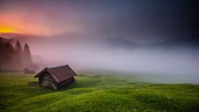 zeitraffer: mystischer nebel in den bayerischen alpen in deutschland - blockhütte stock-videos und b-roll-filmmaterial