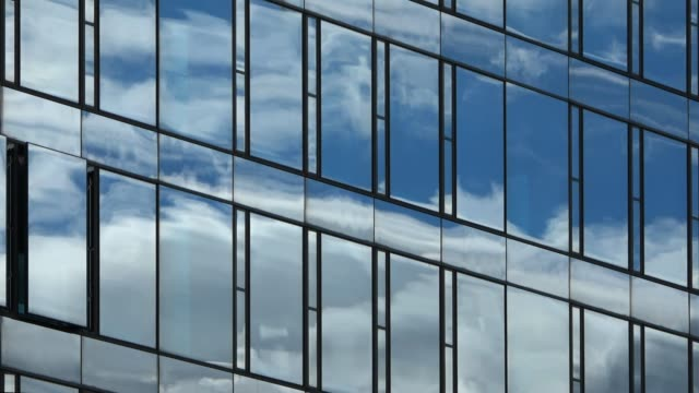 Time lapse of a blue summer sky with clouds reflecting off the glass facade of an office building Time lapse of a blue summer sky with clouds reflecting off the glass facade of an office building skyscraper stock videos & royalty-free footage
