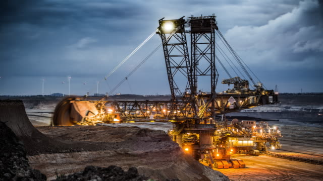Time Lapse of a Bucket Wheel Excavator in a Lignite Surface Mine Dusk to night time lapse of a giant Bucker Wheel Excavator machine digging in brown coal open cast mine Garzweiler in North Rhine Westphalia. Moody twilight sky, excavator already illuminated. Mining Industry in Europe. mining natural resources stock videos & royalty-free footage