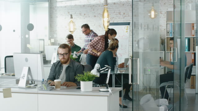 time lapse of a busy creative office. office people working at their personal computers, talking on the phone, moving around. at the conference table business discussion is taking place. - office job stock videos and b-roll footage