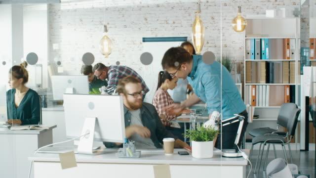 vidéos et rushes de laps de temps d'un bureau de création occupé. les gens de bureau travaillant à leurs ordinateurs personnels, parlant au téléphone, se déplaçant autour. lors de la table de conférence, la discussion commerciale se déroule. - mode bureau