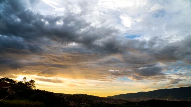 vídeos de stock, filmes e b-roll de lapso de tempo de uma sequência dia a noite com nuvens se movendo rápido e raios solares brilhando sobre as nuvens altas. as luzes da cidade se acendem lentamente ao entrar na noite. - nublado
