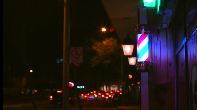 time lapse of a lighted barber pole spinning with nighttime traffic behind video