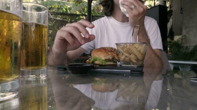 vídeos de stock, filmes e b-roll de lapso de tempo de um homem comendo um hambúrguer e batata frita e beber cerveja - junk food