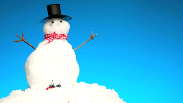 Time Lapse of A Small Snowman Melting Time Lapse footage shot in a studio of a miniature snow man sitting on a mound of snow melting over time. Blue sky background. snowman stock videos & royalty-free footage